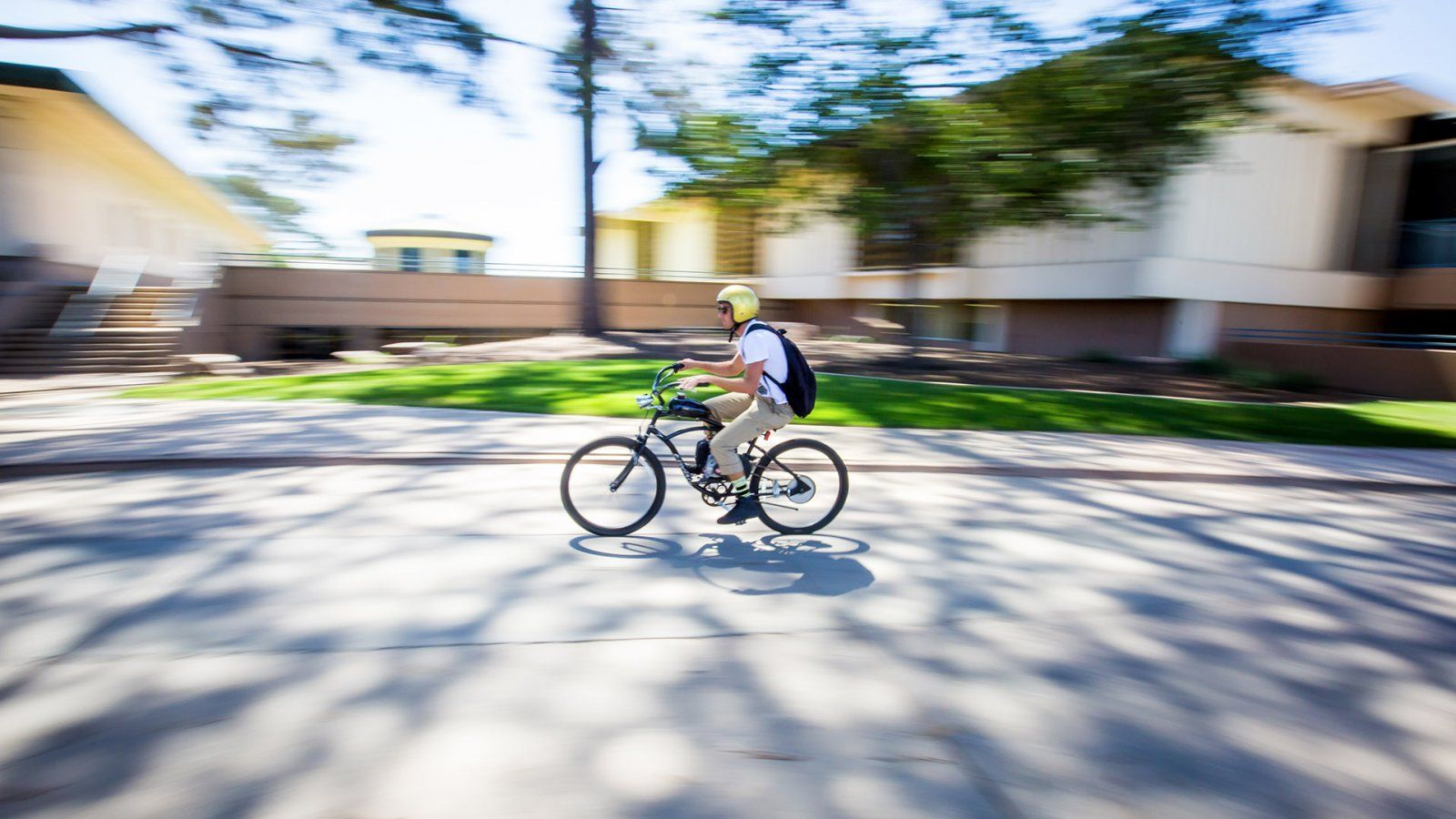A student wizzes through campus on his bike