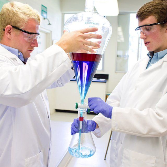 Two male students experimenting with two liquids during a research lab