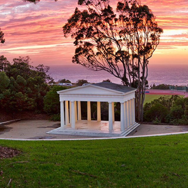 A vibrant orange and purple sunset in San Diego is framed by the iconic Greek Amphitheater on PLNU's campus