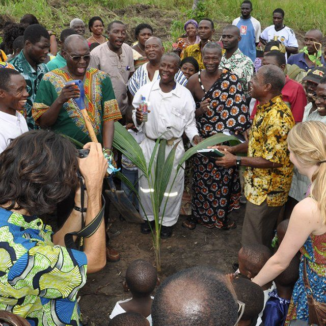 Dr. Adjibolosoo helpign to plant a new tree with a group of surrounding people at the Human Factor Leadership Academy in Ghana