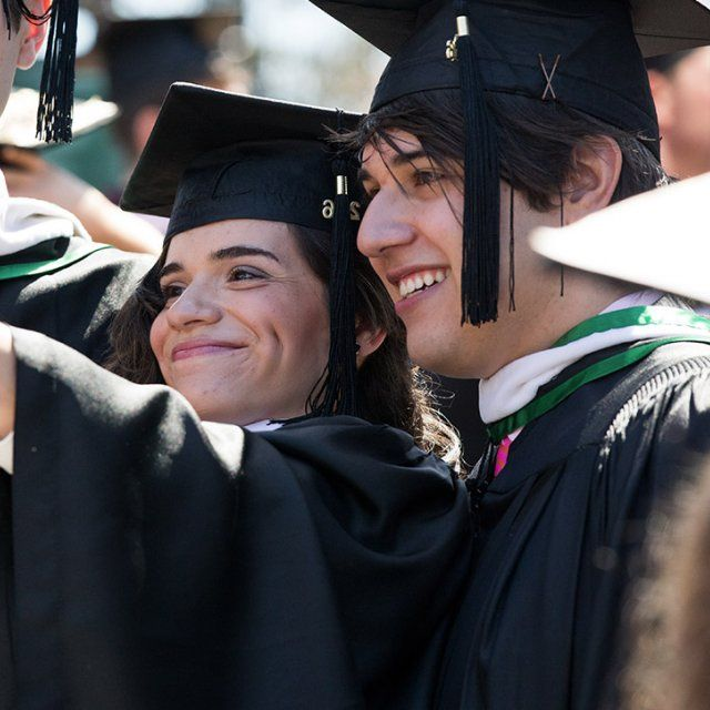 Students at Point Loma Nazarene University smiling while taking a selfie at graduation in full cap and gown