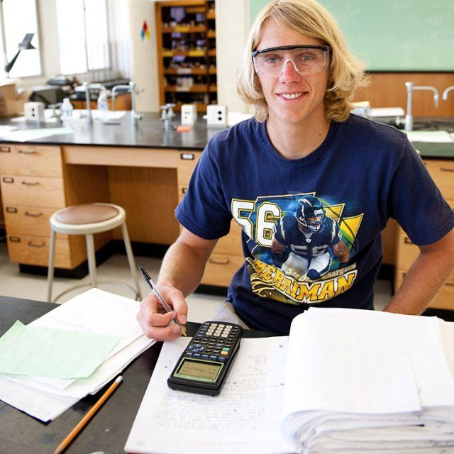 A male science student wearing laboratory safety glasses looks up and smiles from calculating a physics equation
